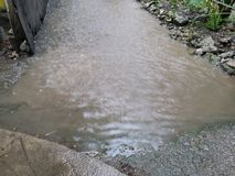 Flooding. Water buildup during a heavy rainstorm is directed down a walkway and out to a service road to prevent flooding a building directly downhill Stock Photo