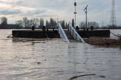 Flooding in winter on the Rhine with a bridge and flotsam.  Royalty Free Stock Image