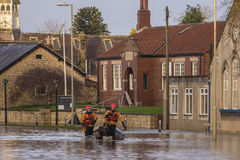 Flooding - Yorkshire - England. Flood water flowing down the street after the River Derwent burst its banks in the village of Old Malton in North Yorkshire in Royalty Free Stock Photos