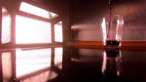 Floodlight lights up the pouring in of a glass of wine in slow motion stock video