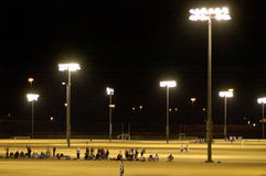 Floodlights. Being used to illuminate a night-time soccer game Royalty Free Stock Images