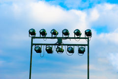 Floodlights in blue sky with clouds. Green Floodlights in blue sky with clouds Royalty Free Stock Photos