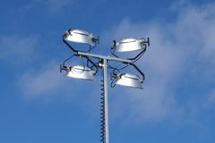 Floodlights on pole. Bright lights overhead illuminate construction areas. Visibility is important for security and safety Stock Photo