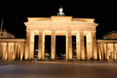 The floodlit Brandenburg Gate in Berlin with a few fleeting shad. Ows of anonymous Berliner`s - Symbol of Germany royalty free stock image