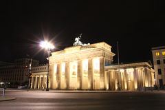 The floodlit Brandenburg Gate in Berlin with a few fleeting shad. Ows of anonymous Berliner`s - Symbol of Germany royalty free stock photography