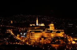 Floodlit Buda Royal Castle with bastions and Matthias Church. Floodlit Buda Castle Hill elevated view in evening lit by exterior lighting with Baroque Royal stock photography