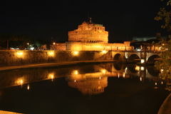 Floodlit castle at night. The floodlit Castel Sant Angelo reflected in the River Tiber in Rome in Italy stock photography