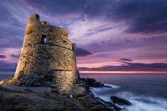 Floodlit Genoese tower at Erbalunga in Corsica at sunrise. Floodlit Genoese stone tower at Erbalunga on the coast of Cap Corse in Corsica as a dramatic orange stock photography