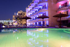 Floodlit hotel. Ultramodern floodlit hotel with balconies and large swimming pool stock photography