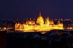 Floodlit Hungarian Parliament Building at dusk on Danube bank. Panorama of Neo-Gothic Orszaghaz Parliament Building Hungarian legislative body seat at dusk royalty free stock photo