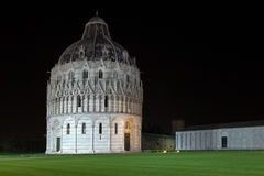 Floodlit Pisa Baptistry of St John at night. Floodlit Pisa Baptistry of St John near the leaning tower of Pisa in Italy against a dark night sky stock image