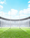 Floodlit Stadium Day. A generic seated aussie rules stadium showing goal posts on a green grass pitch in the day time under a blue cloudy sky - 3D render stock illustration