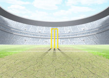 Floodlit Stadium Day. A generic seated cricket stadium with cracked pitch and yellow wickets a green grass pitch in the day time under a blue cloudy sky - 3D Stock Photo