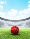 Floodlit Stadium Day. A generic seated cricket stadium with a red ball on a green grass pitch in the day time under a blue cloudy sky - 3D render stock illustration