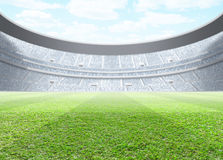 Floodlit Stadium Day. A generic seated stadium with a green grass pitch in the day time under a blue cloudy sky - 3D render Stock Photo