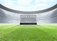 Floodlit Stadium Day. A generic seated lawn hockey stadium with a netted goal on a green grass pitch in the day time under a blue cloudy sky - 3D render royalty free illustration