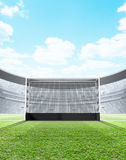 Floodlit Stadium Day. A generic seated lawn hockey stadium with a netted goal on a green grass pitch in the day time under a blue cloudy sky - 3D render stock illustration