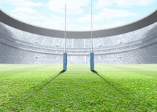 Floodlit Stadium Day. A generic seated rugby stadium showing a set of padded goal posts on a green grass pitch in the day time under a blue cloudy sky - 3D stock illustration
