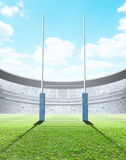 Floodlit Stadium Day. A generic seated rugby stadium showing a set of padded goal posts on a green grass pitch in the day time under a blue cloudy sky - 3D vector illustration