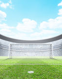 Floodlit Stadium Day. A generic seated soccer stadium showing a set of goals and penalty spot in the day time under a blue cloudy sky - 3D render royalty free illustration