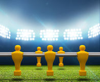 Floodlit Stadium With Foosball Players. A football stadium with an unmarked green grass pitch and a row of yellow foosball players on it at night under royalty free illustration