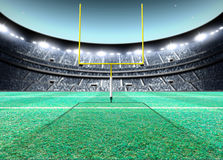 Floodlit Stadium Night. A generic seated american football stadium with yellow goal posts on a green grass pitch at night under illuminated floodlights - 3D Stock Image