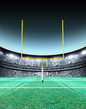 Floodlit Stadium Night. A generic seated american football stadium with yellow goal posts on a green grass pitch at night under illuminated floodlights - 3D Royalty Free Stock Photo
