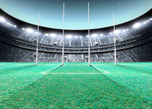 Floodlit Stadium Night. A generic seated aussie rules stadium showing goal posts on a green grass pitch at night under illuminated floodlights - 3D render royalty free illustration