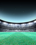 Floodlit Stadium Night. A generic seated stadium with a green grass pitch at night under illuminated floodlights - 3D render Royalty Free Stock Photo