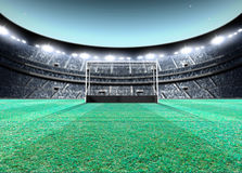 Floodlit Stadium Night. A generic seated lawn hockey stadium with a netted goal on a green grass pitch at night under illuminated floodlights - 3D render Stock Images