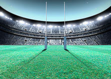 Floodlit Stadium Night. A generic seated rugby stadium showing a set of padded goal posts on a green grass pitch at night under illuminated floodlights - 3D Stock Photo