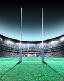 Floodlit Stadium Night. A generic seated rugby stadium showing a set of padded goal posts on a green grass pitch at night under illuminated floodlights - 3D stock illustration