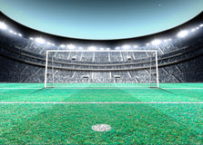 Floodlit Stadium Night. A generic seated soccer stadium showing a set of goals and penalty spot on a green grass pitch at night under illuminated floodlights Stock Image