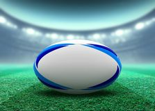 Floodlit Stadium And Rugby Ball. A reguar white rugby ball with blue design elements resting on a stadium grass pitch at night under illuminated floodlights - 3D vector illustration