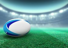 Floodlit Stadium And Rugby Ball. A reguar white rugby ball with blue design elements resting on a stadium grass pitch at night under illuminated floodlights - 3D royalty free illustration