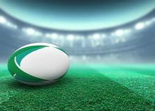 Floodlit Stadium And Rugby Ball. A reguar white rugby ball with green design elements resting on a stadium grass pitch at night under illuminated floodlights vector illustration
