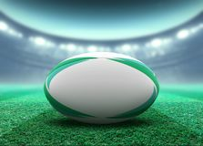 Floodlit Stadium And Rugby Ball. A reguar white rugby ball with green design elements resting on a stadium grass pitch at night under illuminated floodlights stock illustration