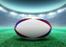 Floodlit Stadium And Rugby Ball. A reguar white rugby ball with red and blue design elements resting on a stadium grass pitch at night under illuminated vector illustration