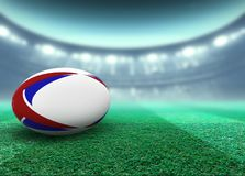 Floodlit Stadium And Rugby Ball. A reguar white rugby ball with red and blue design elements resting on a stadium grass pitch at night under illuminated royalty free illustration