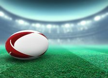 Floodlit Stadium And Rugby Ball. A reguar white rugby ball with red design elements resting on a stadium grass pitch at night under illuminated floodlights - 3D stock illustration