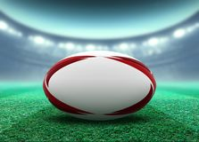 Floodlit Stadium And Rugby Ball. A reguar white rugby ball with red design elements resting on a stadium grass pitch at night under illuminated floodlights - 3D royalty free illustration