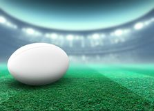 Floodlit Stadium And Rugby Ball. A reguar white rugby ball resting on a stadium grass pitch at night under illuminated floodlights - 3D render stock illustration