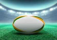 Floodlit Stadium And Rugby Ball. A reguar white rugby ball with yellow and green design elements resting on a stadium grass pitch at night under illuminated royalty free illustration