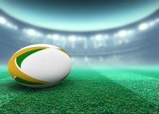 Floodlit Stadium And Rugby Ball. A reguar white rugby ball with yellow and green design elements resting on a stadium grass pitch at night under illuminated stock illustration