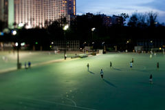 Floodlit urban soccer pitch. Footballers playing on floodlit soccer pitch at night in Hong Kong city, China stock photography