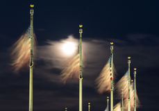 Floodlit view of flags by Washington Monument. US Flags flutter in front of moon by Washington Monument on a clear night in Washington DC, United States of stock photography