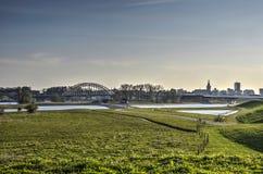 Floodplains near Nijmegen, the Netherlands. View across the grassy floodplains towards the bridge across the river Waal and the city of Nijmegen, The Netherlands Stock Image