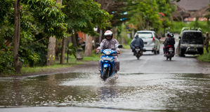 Floods. LAKE BATUR, BALI - JANUARY 21. Man driving through flooded street after downpour on Lake Batur on January 21, 2012 in Bali, Indonesia. Weather patterns Stock Photos