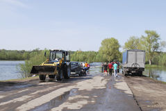 Floods, it flooded road tractor carries cars. Stock Photos