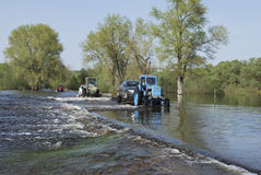 Floods, it flooded road tractor carries cars. Royalty Free Stock Images